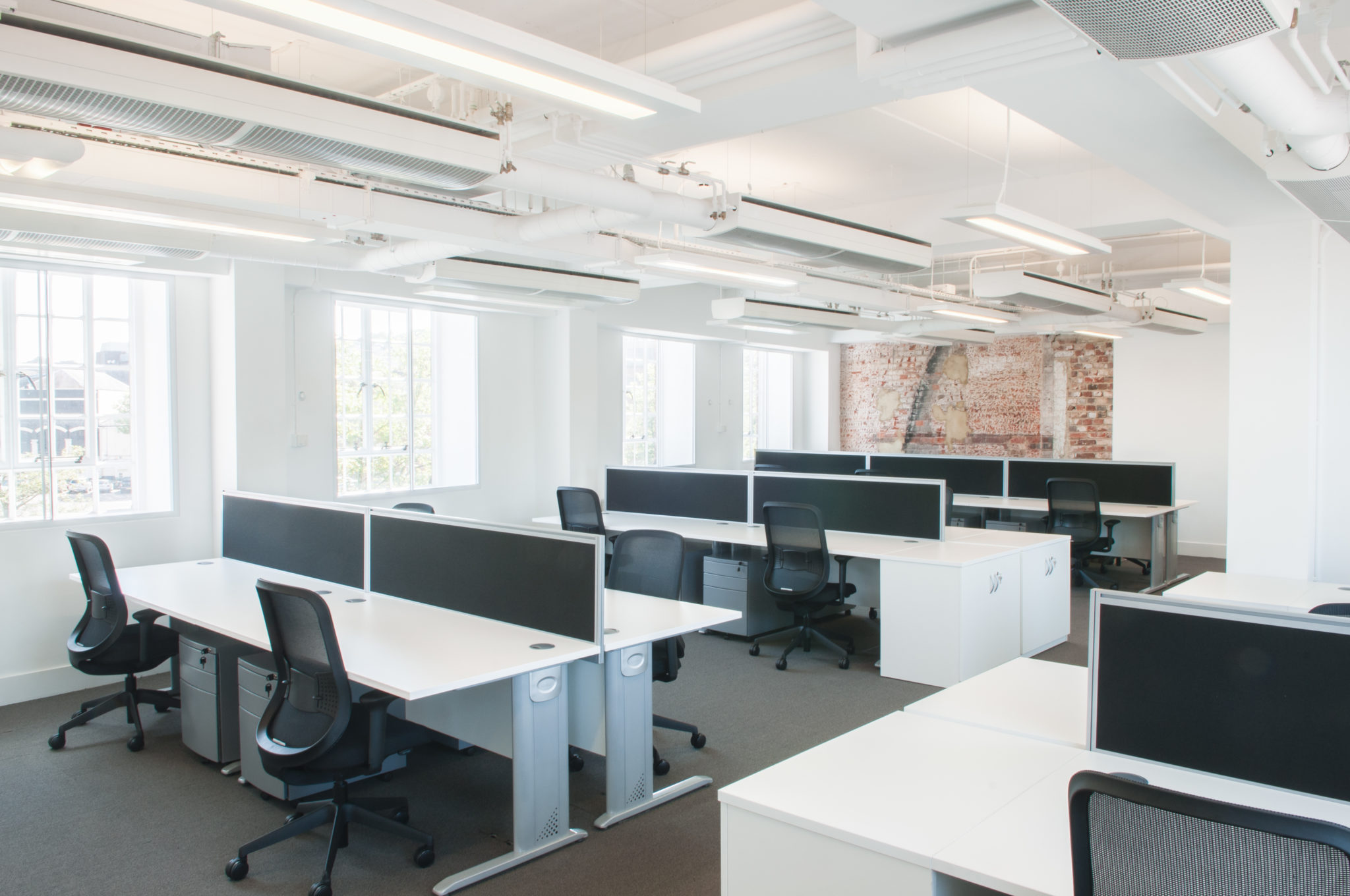 Open plan office with original brickwork feature wall
