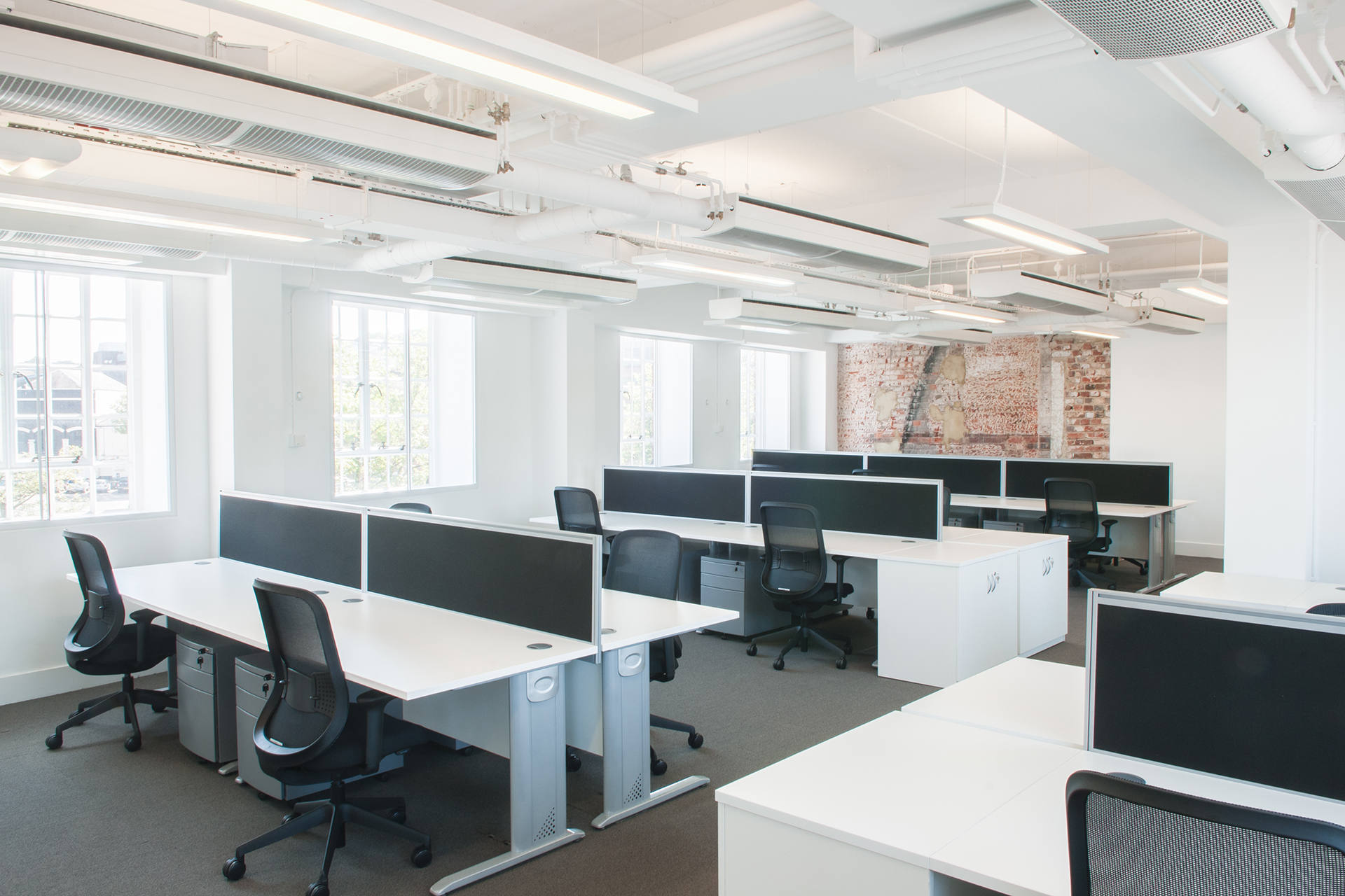 open plan office with exposed brick wall