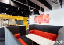 Acoustic panels suspended from an exposed ceiling