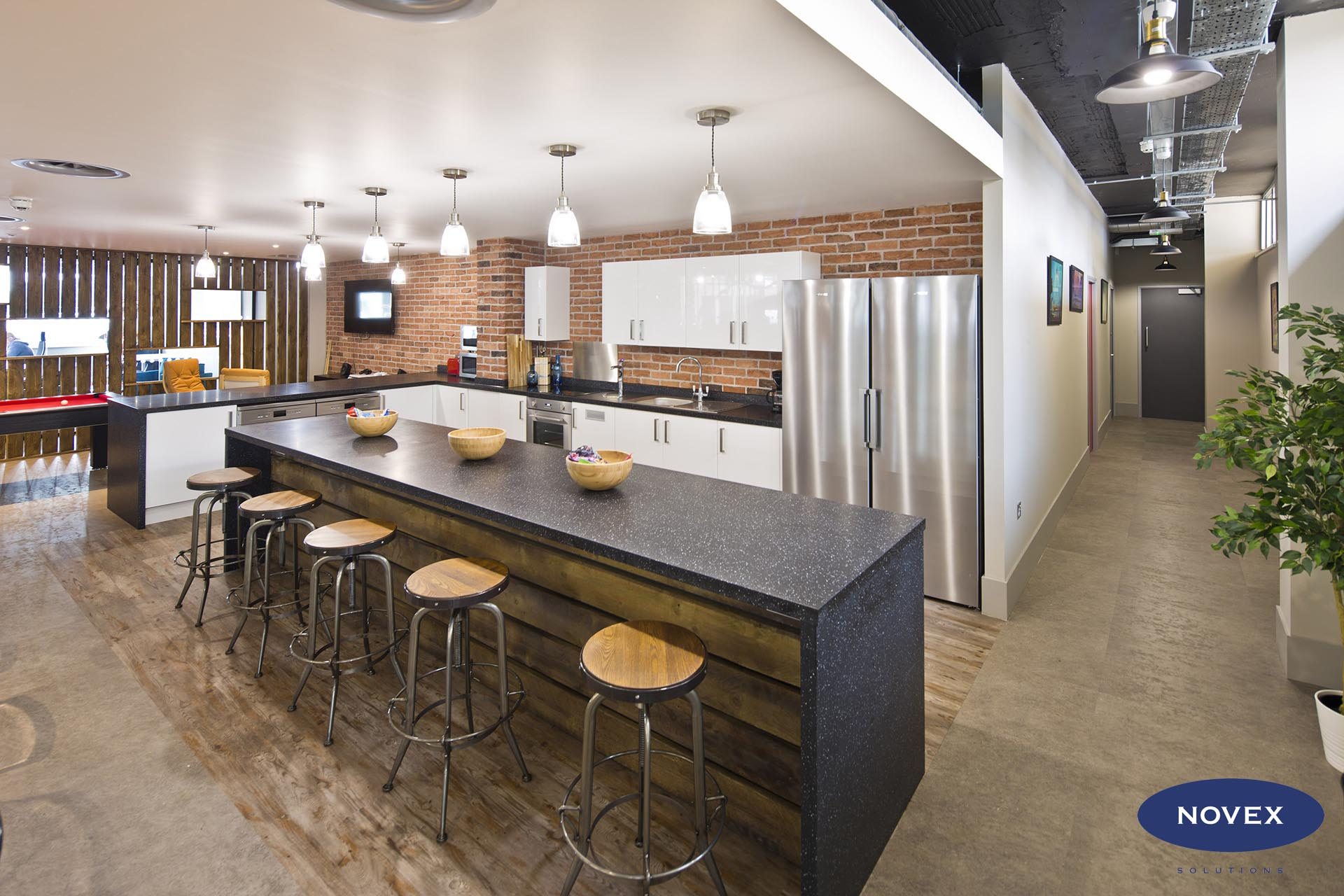 exposed brick wall and timber breakfast bar with white gloss kitchen and black tops